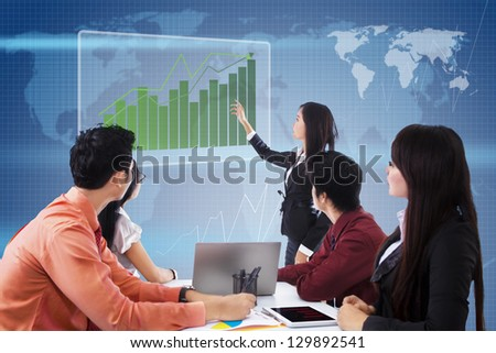 Business meeting with presentation and profit bar chart on blue world map background - stock photo
