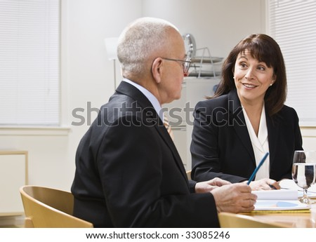 Business meeting with senior male and attractive female at desk. Horizontal - stock photo
