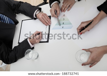 Business meeting with three employees, chart analysis