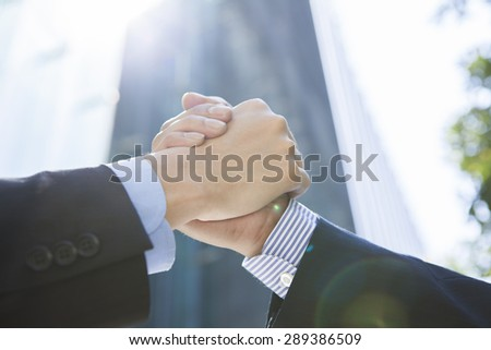 Business men and woman outside in front of tower building shaking hands  - stock photo