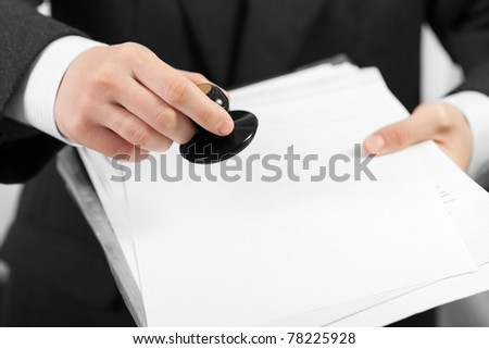 Business men hand hold office paper document stamp - stock photo