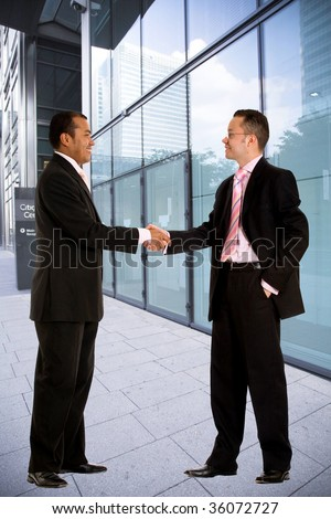Business men handshaking outside a corporate building
