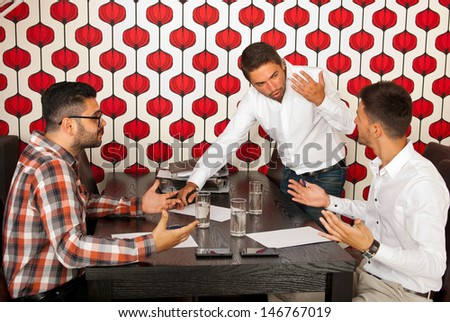 Business men having serious discussion at meeting in modern office - stock photo