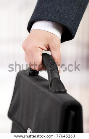 Business men in black suit hand holding briefcase - stock photo