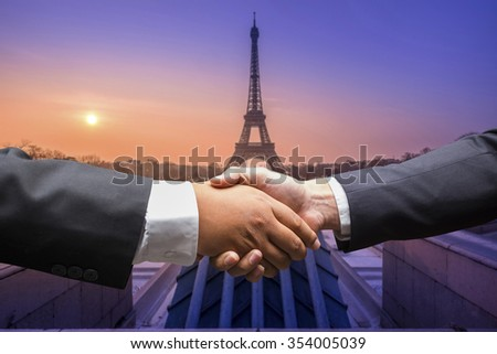 Business men shaking hands in paris,France - stock photo
