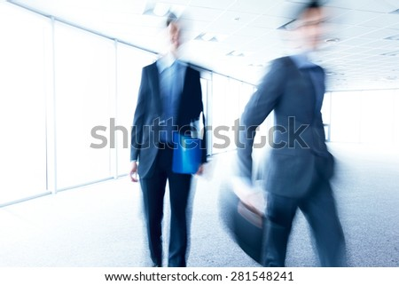 business men walking through office blurred - stock photo