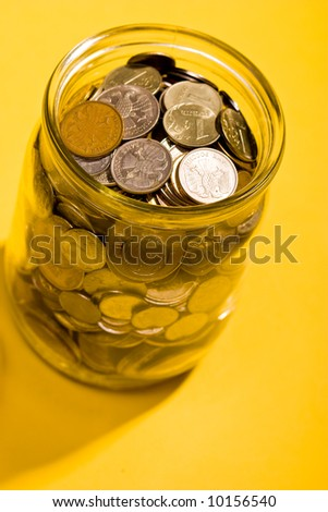 business metaphor: glassy jar with Russian coins over yellow