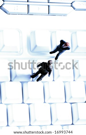 business miniature figurines standing on a blank computer keyboard - stock photo
