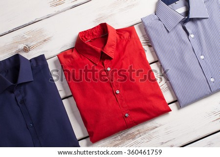 Business modern men's shirts with different colors and prints on white wooden background.