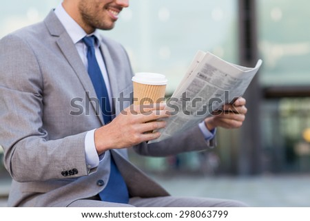 business, news, break and people and concept - close up of smiling businessman reading newspaper and drinking coffee from paper cup over office building - stock photo