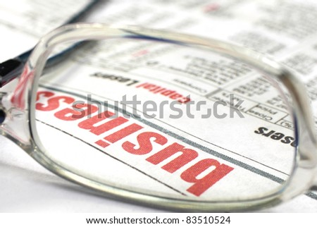 Business news in a newspaper with spectacles - stock photo