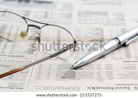 Business newspaper and glasses. Conceptual image of opened newspaper with stock exchange data, glasses and pen. - stock photo