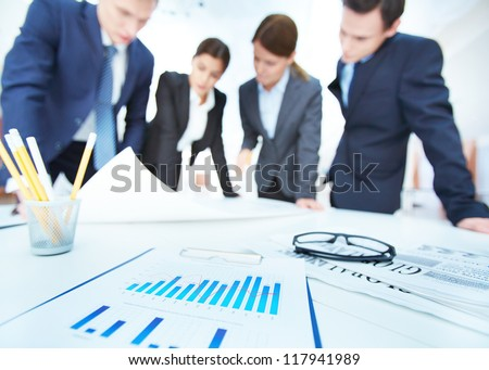 Business objects on background of engineers discussing blueprint at meeting - stock photo