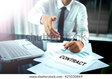 Business offering a handshake and contract - stock photo