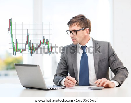 business, office and money concept - businessman in suit and black eyeglasses with laptop computer, papers, calculator and forex chart - stock photo