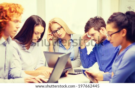 business, office and startup concept - depressed creative team with table pc and laptop computers working in office - stock photo