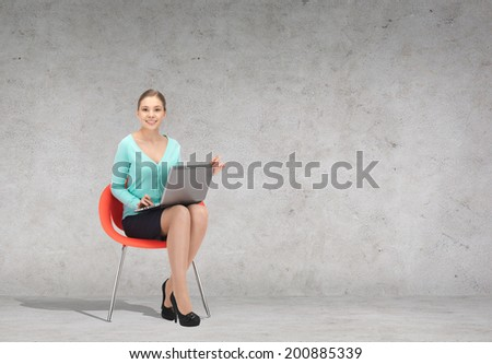 business, office and technology concept - young businesswoman sitting in chair with laptop - stock photo