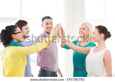 business, office, gesture and startup concept - smiling creative team doing high five gesture in office - stock photo