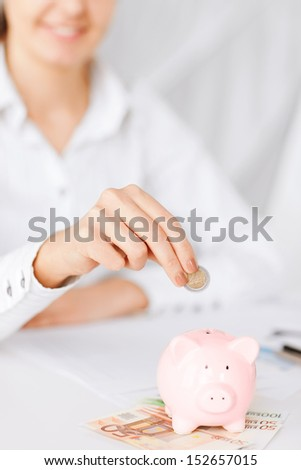 business, office, household, school, tax and education concept - woman hand putting coin into small piggy bank - stock photo