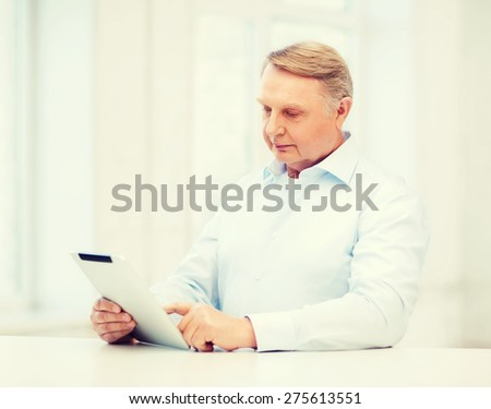 business, office, oldness, school and education concept - old man wearing eyeglasses with tablet computer at home - stock photo