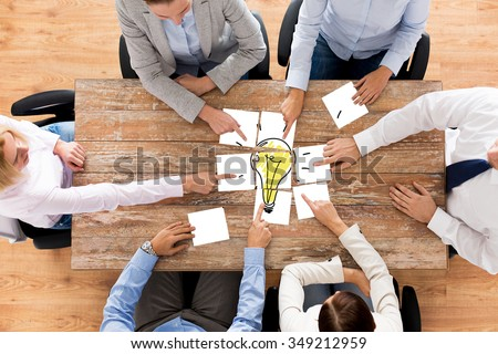 business, office people, startup and teamwork concept - close up of creative team sitting at table and putting together puzzle pieces with light bulb picture - stock photo