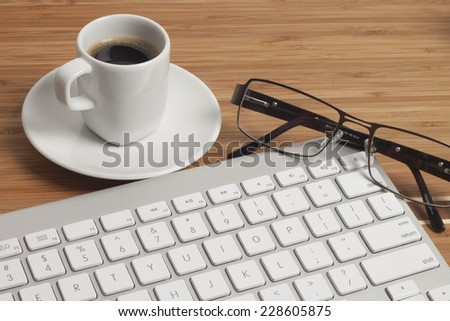 Business Office scenario, keyboard, Note Pad, glasses, tablet, pencil and coffee on work surface - stock photo