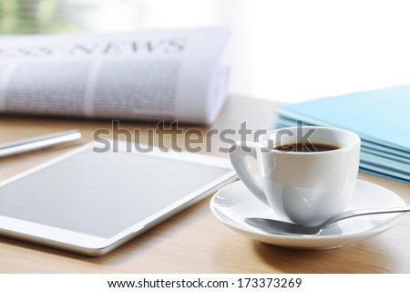 Business Office scene, digital tablet and newspaper with coffee  - stock photo