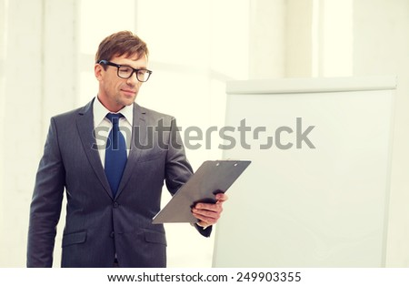 business, office, school and education concept - businessman pointing to flip board in office - stock photo