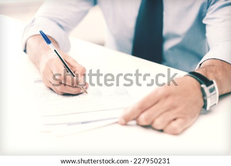 business, office, school and education concept - man signing a contract - stock photo