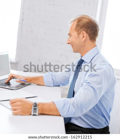 business, office, school and education concept - smiling businessman working in office