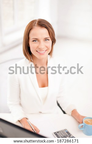 business, office, school and education concept - smiling businesswoman with computer, documents and coffee
