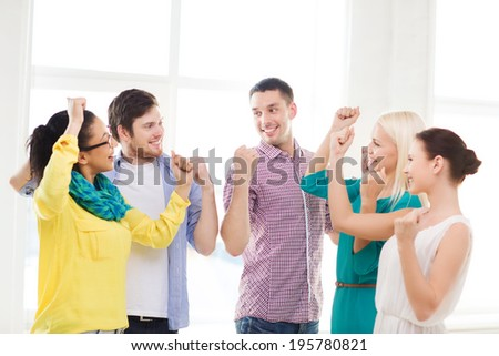 business, office, startup, success and victory concept - happy creative team celebrating victory in office - stock photo