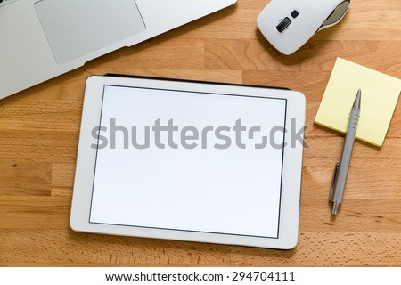 Business office table with table pc presenting a blank screen for advertising