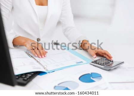 business, office, tax, school and education concept - woman hand with calculator and papers - stock photo