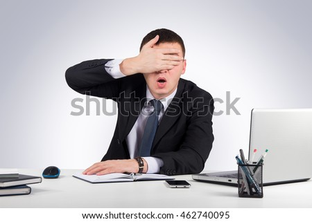 Business,office, technology, finances and internet concept-Frustrated businessman close his eyes by hand on gray background