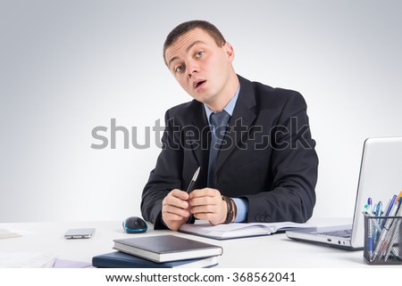 Business,office, technology, finances and internet concept - Serious businessman skeptically looking at you sitting at his desk on gray background.Human face expression  - stock photo
