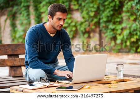 Business on fresh air. Confident young man working on laptop while sitting at the wooden table outdoors - stock photo