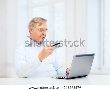 business, online banking, internet shopping and oldness concept - smiling old man with laptop computer and credit card at home - stock photo