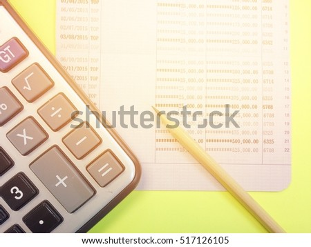 Business or finance background concept : Calculator, pencil and savings account passbook on yellow background