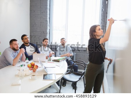 Business or freelance workshop session. Young businesswoman writing new business plan or strategy for companies, enterprises or firms while performing in board room in office. - stock photo