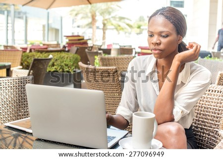 Business outside the office in Dubai. African businesswoman businessman working on a laptop at a cafe table in Downtown Dubai - stock photo