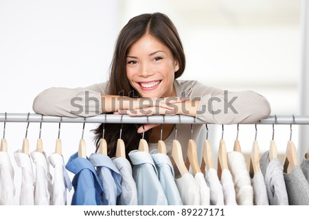 Business owner - clothes store. Young female business owner in her shop behind clothes rack smiling proud and happy. Multicultural Caucasian / Asian female model. - stock photo