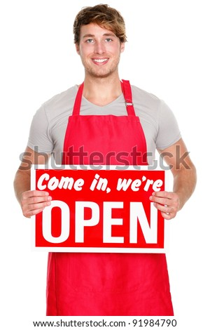 Business owner / employee showing open sign. Man wearing red apron smiling happy. Caucasian male model. - stock photo