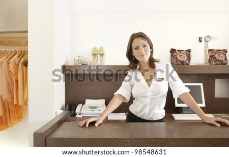 Business owner leaning on her fashion store's desk, feeling proud. - stock photo