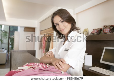 Business owner leaning with crossed arms on her store's payment area, feeling proud. - stock photo