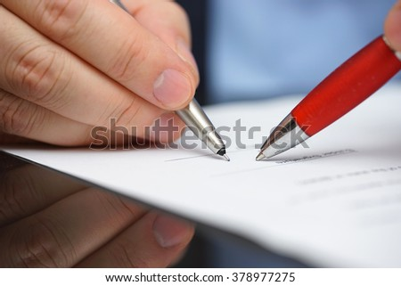 business partner is showing client where to sign partnership - stock photo
