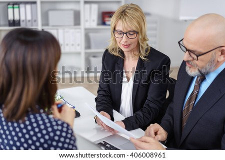 Business partners, a middle-aged man and woman, conducting a job interview reading the female applicants CV with serious expressions - stock photo