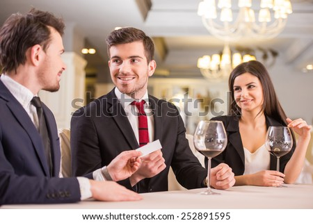 Business partners are changing business cards during a meeting in restaurant. - stock photo