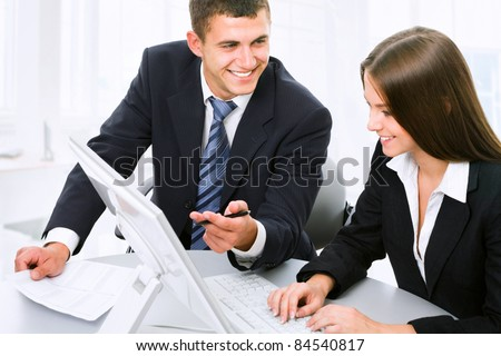 Business partners are discussing a new project while sitting at the computer - stock photo