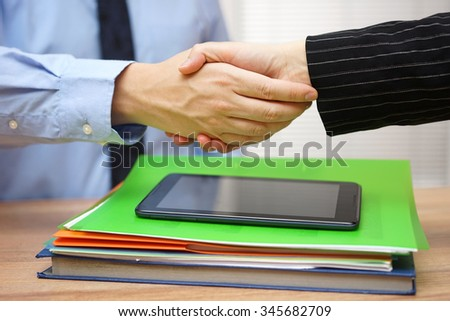 Business partners are handshaking  over business documentation,collaboration concept - stock photo